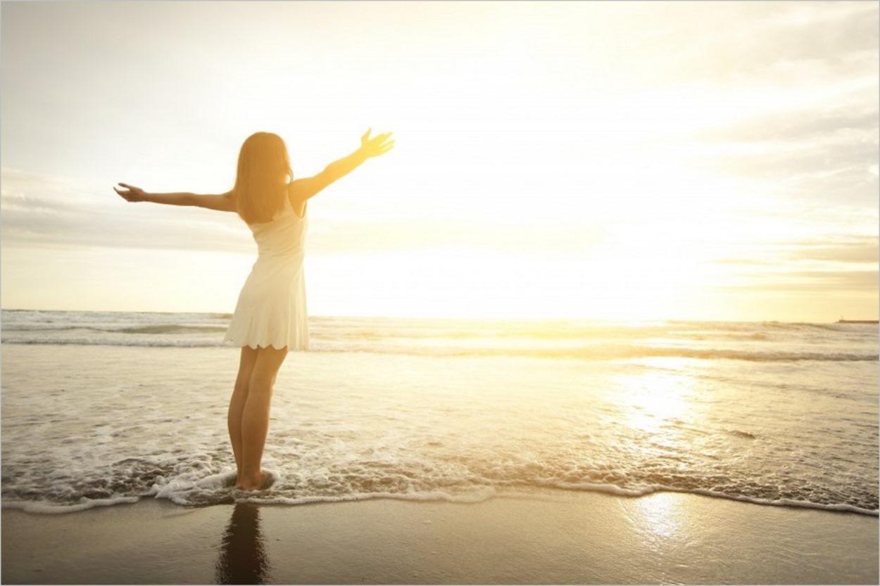 Femme heureuse sur une plage au bord de l'eau