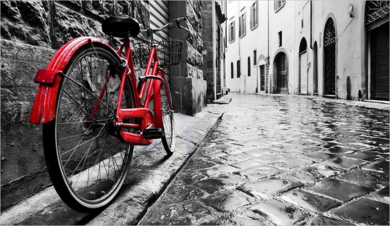 Un vélo rouge dans un décor en noir et blanc